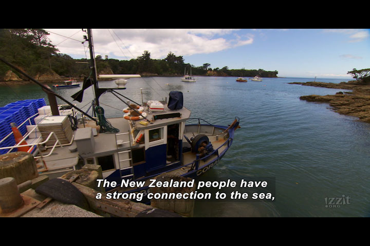 Coastal bay with a docked boat. Caption: The New Zealand people have a strong connection to the sea,
