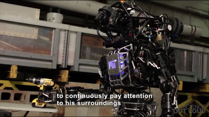 A humanoid robot holding a drill. Caption: to continuously pay attention to his surroundings