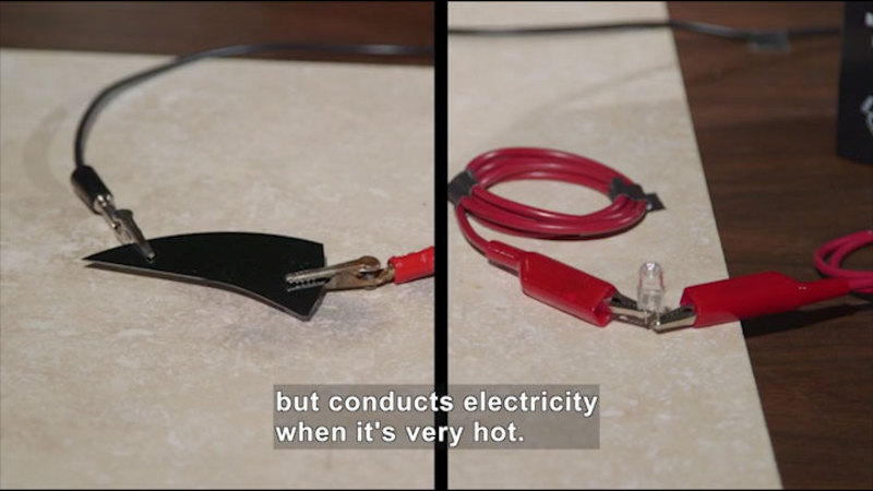 Two conductors attached to objects. Caption: but conducts electricity when it's very hot.
