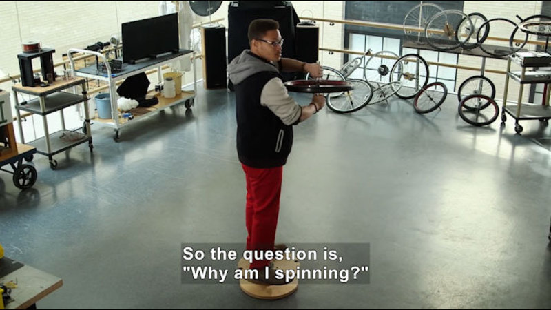 """Person standing on a round platform holding a wheel. Caption: so the question is, """"Why am I spinning?"""""""