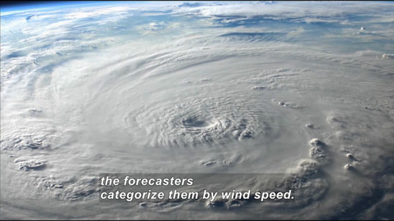 A large circular storm on Earth's surface, as seen from space. Caption: the forecasters categorize them by wind speed.