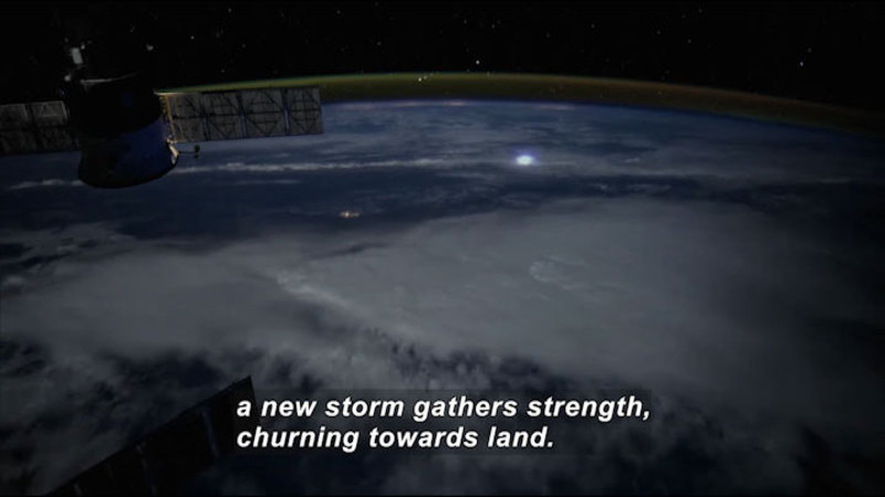 Satellite looking down the surface of the Earth over a large storm system. Caption: a new storm gathers strength, churning towards land.