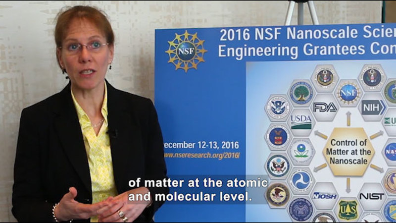 """Person speaking and standing next to a poster board with """"Control of matter at the nanoscale"""" surrounded by logos from different organizations. Caption: of matter at the atomic and molecular level."""