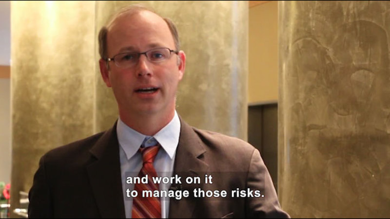 Person speaking. Caption: and work on it to manage those risks.