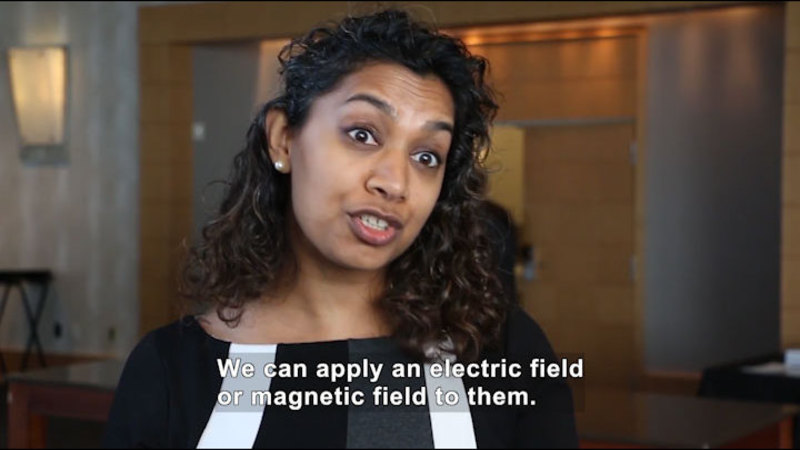 Person speaking. Caption: We can apply an electric field or magnetic fields to them.