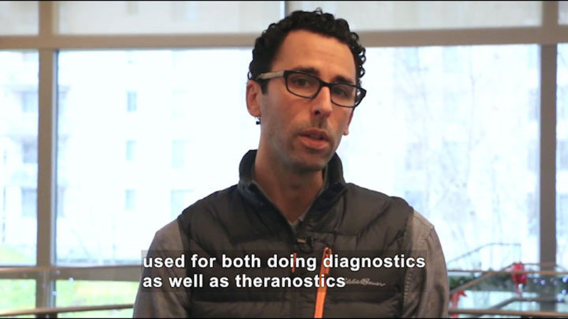 Person speaking. Caption: used for both doing diagnostics as well as theranostics.