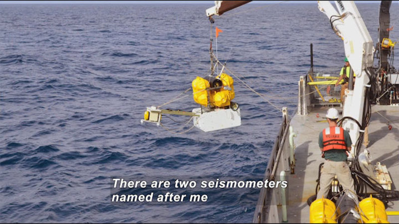 Ship with industrial equipment and a crane lowering something into the water. Caption: There are two seismometers named after me