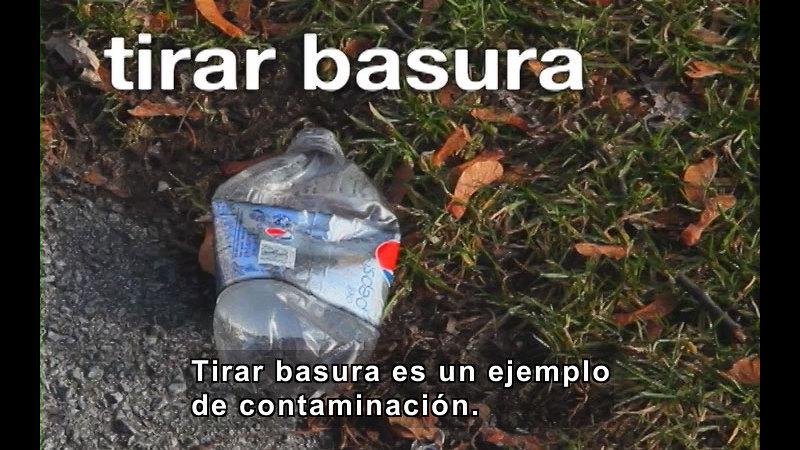Crushed plastic soda bottle on the ground. Spanish captions.
