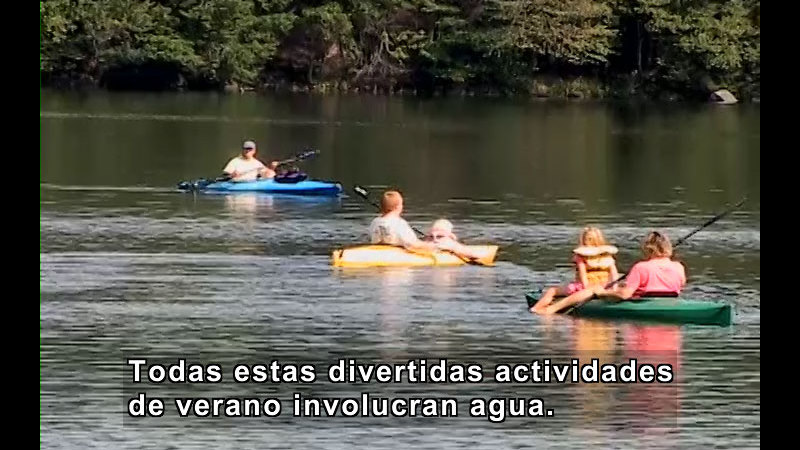 People in kayaks paddling on the water. Spanish captions.