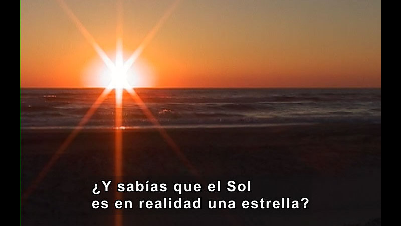 Sunset over the ocean. Spanish captions.