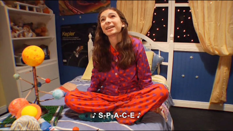 Young girl sitting in her bed singing. Caption: S-P-A-C-E