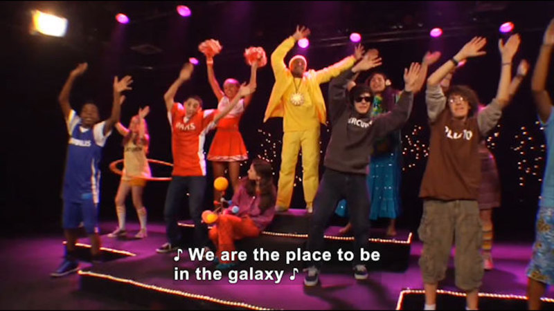 Group of young people singing and dancing. Caption: We are the place to be in the galaxy
