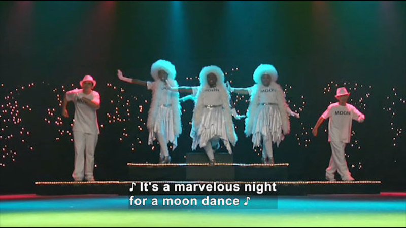 Five people dancing and singing. Caption: It's a marvelous night for a moon dance