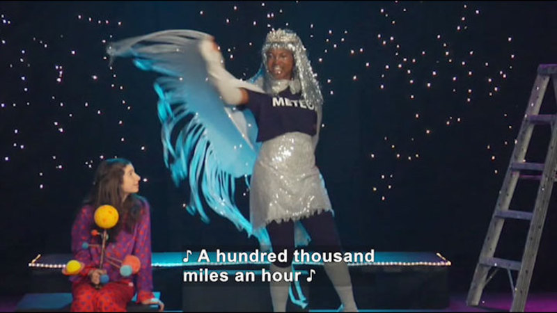 Two people, one of them singing. Caption: A hundred thousand miles an hour
