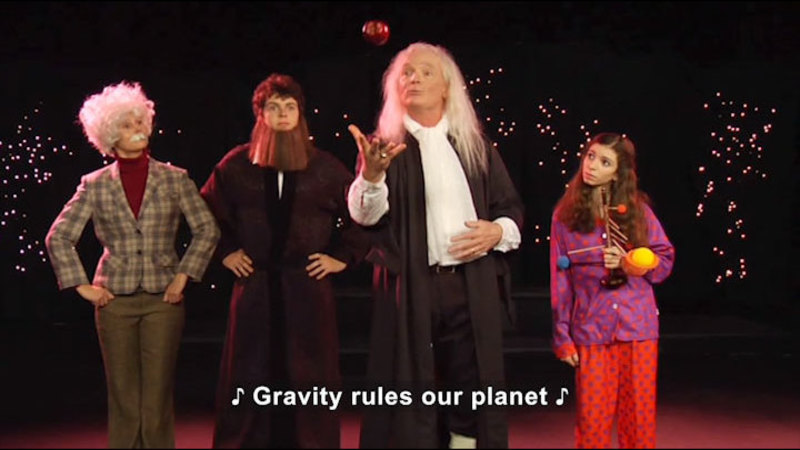 Four people, one man tossing an apple into the air. Caption: Gravity rules our planet