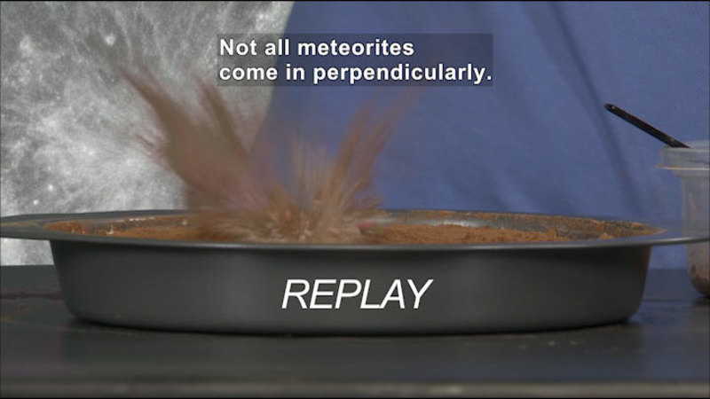Object striking dirt and throwing up debris. REPLAY. Caption: Not all meteorites come in perpendicularly.