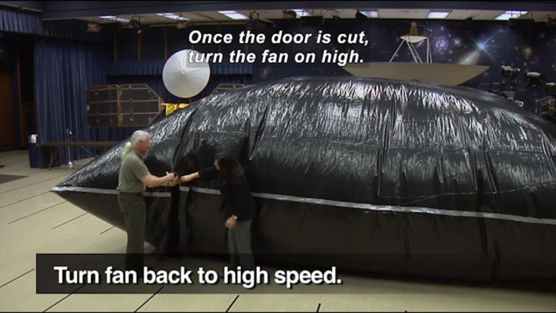 People standing in front of a giant inflated black plastic pouch. Turn fan back to high speed. Caption: Once the door is cut, turn the fan on high.