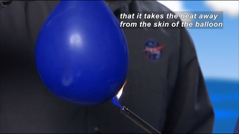 Person wearing a jumpsuit with a NASA logo holds a flame to an inflated balloon. Caption: that it takes the heat away from the skin of the balloon