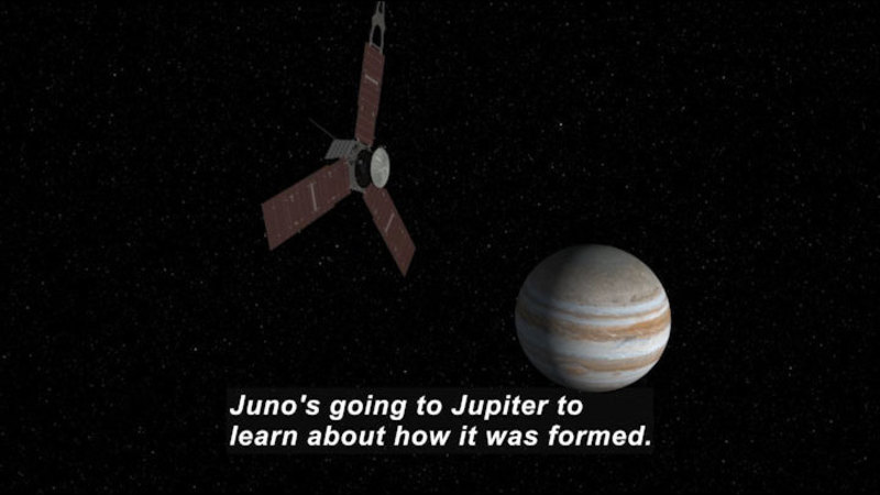 A hexagonal space craft with three much larger wings equally spaced around the hexagonal base flying in space with the planet Jupiter in the distant background. Caption: Juno's going to Jupiter to learn about how it was formed.