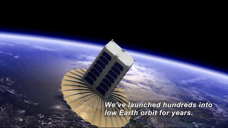 A rectangular space craft with a large, flat round disc pointed towards the planet earth, visible in the background. Caption: We've launched hundreds into low Earth orbit for years.