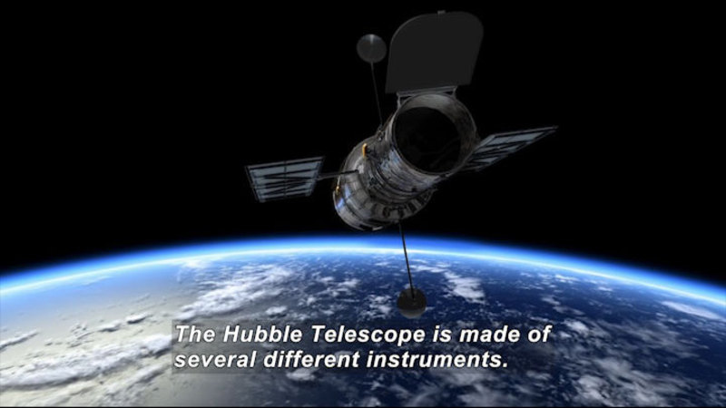 A cylindrical space craft with two solar wings and two rods capped in spheres protruding from it in relief over the planet Earth and space. Caption: The Hubble Telescope is made of several different instruments.