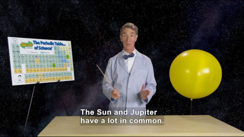 Man teaching at a table. Caption: The Sun and Jupiter have a lot in common.