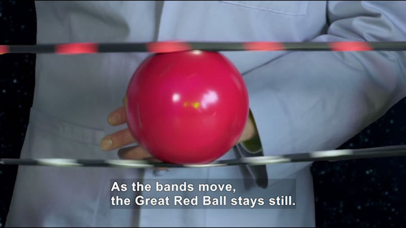 A ball between two bands. Caption: As the bands move, the Great Red Ball stays still.
