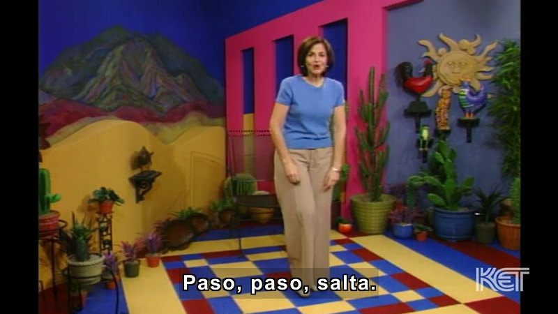 Person standing in a colorful room with cacti in pots all around the walls. Spanish captions.