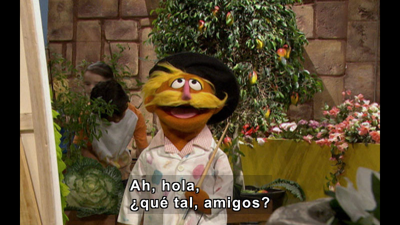 Character wearing a painting smock and holding a paintbrush, standing in front of a canvas. Spanish captions.