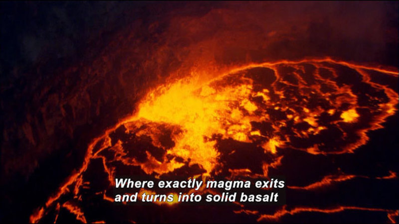 Glowing lava as seen from above. Caption: Where exactly magma exits and turns into solid basalt