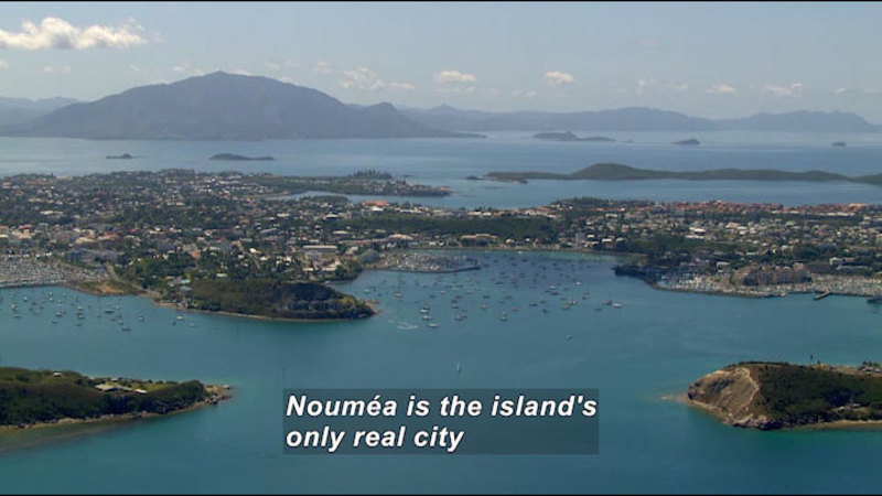 Aerial view of a populated island surrounded by bluish green water. Caption: Nouméa is the island's only real city