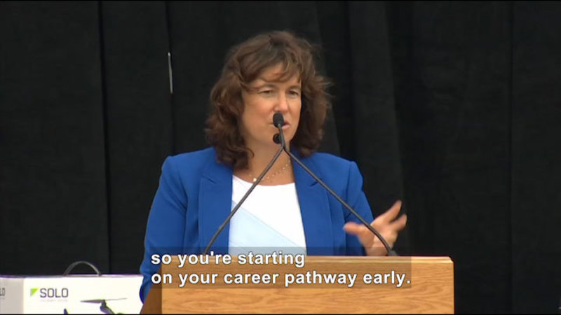 Woman speaking into a microphone. Caption: so you're starting on your career pathway early.