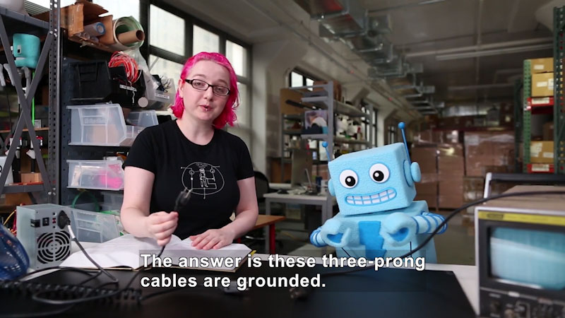 Person in a workshop holding a power cord with three prongs. Caption: The answer is these three-prong cables are grounded.