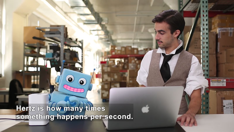 Person and a robot in a workshop with a laptop in front of them. Caption: Hertz is how many times something happens per second.