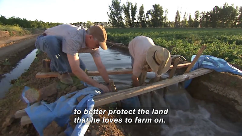 Two people working on an irrigation channel. Caption: to better protect the land that he loves to farm on.