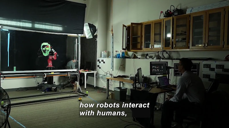 Person at a computer looking at a projection of a wire frame human face on a screen. Caption: how robots interact with humans,
