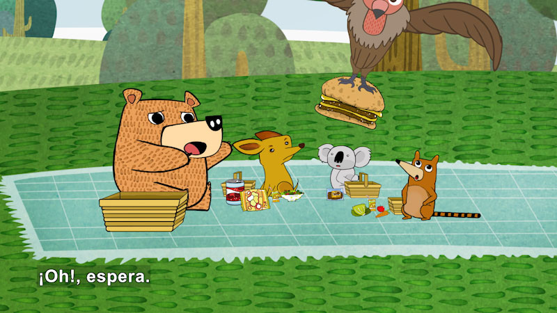 Cartoon of a bear and other animals having a picnic and looking dismayed. A large bird has swooped down and taken a hamburger from their picnic. Spanish captions.