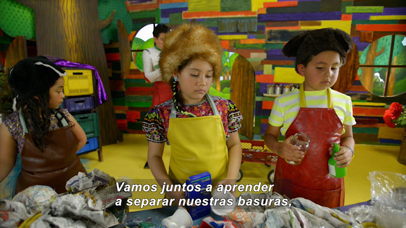Children wearing aprons standing in front of table covered in trash. Spanish captions.