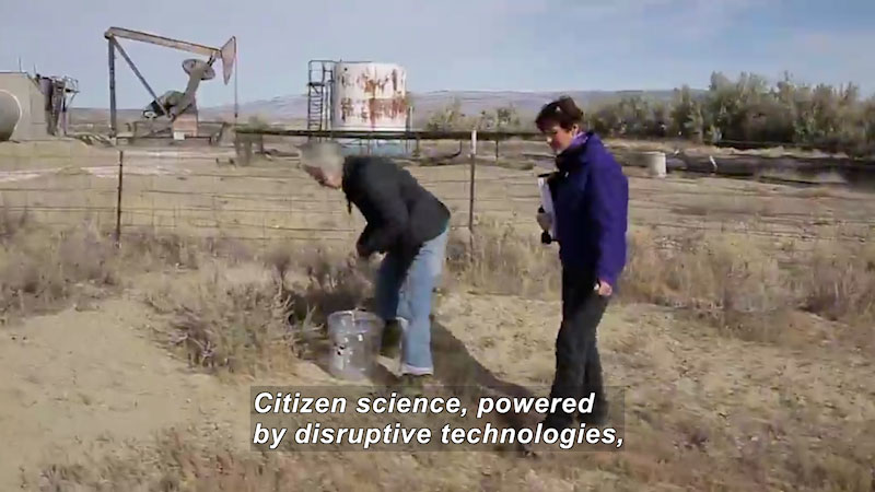 Two citizen scientists investigate an industrial site. One person carries a bucket while the other carries a file in the file. Caption: Citizen science, powered by disruptive technologies,