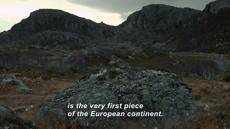 Sparse vegetation on a rocky hillside. Caption: is the very first piece of the European continent.