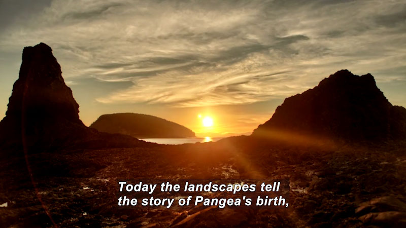 Sun setting between two rocky outcroppings over a body of water. Caption: Today the landscapes tell the story of Pangea's birth,