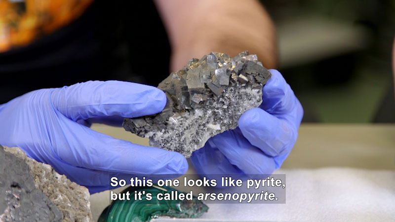 Person holding a silvery rock with geometric chunks on top and white and silver crystalline structures on the bottom. Caption: So this one looks like pyrite, but it's called arsenopyrite.