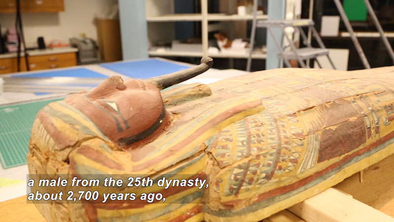 Sarcophagus covered in faded paint. Caption: a male from the 25th dynasty, about 2,700 years ago,