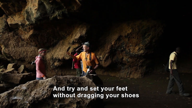 People walking through a cave. Caption: And try and set your feet without dragging your shoes