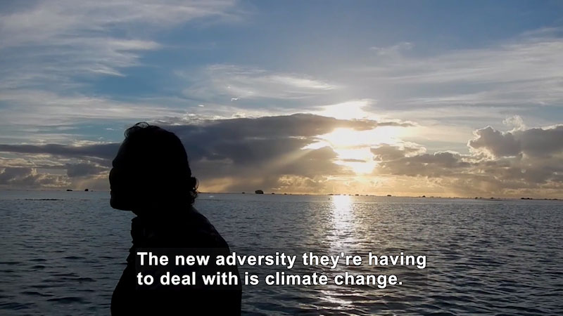 Person in shadow against a backdrop of open expanse of ocean and sky. Caption: The new adversity they're having to deal with is climate change.