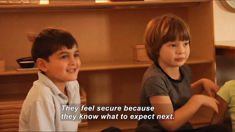 Kids sitting on the floor in a classroom setting. Caption: They feel secure because they know what to expect next.