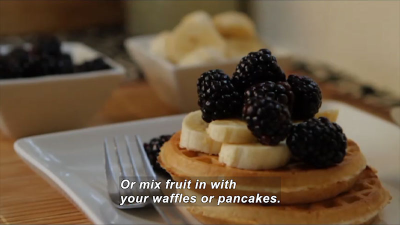 Waffles topped with sliced bananas and blackberries. Caption: Or mix fruit in with your waffles or pancakes.