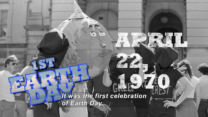 """People with sacks covering their faces and phrases such as """"Greed"""" and """"Self Interest"""" written on their shirts stand next to a person wearing Earth with a face over their head. 1st Earth Day April 22, 1970 Caption: It was the first celebration of Earth Day,"""