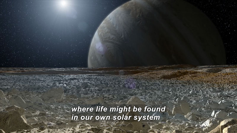 Rocky, flat, barren landscape with a large planet covered in bands of color on the horizon and a star in the distance. Caption: where life might be found in our own solar system