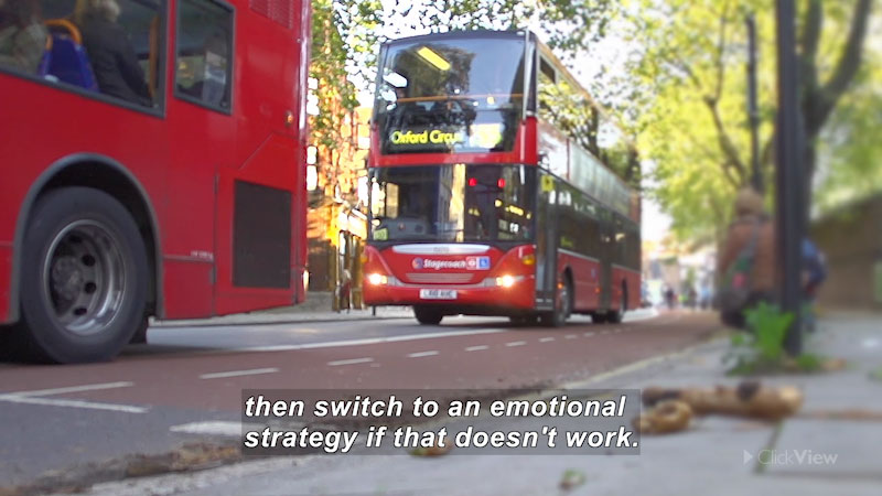 Two double-decker buses driving on a city street. Caption: then switch to an emotional strategy if that doesn't work.